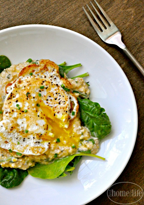 creamy oatmeal with herbs and cheese and a fried egg on top- the perfect easy and healthy breakfast idea via firsthomelovelife.com