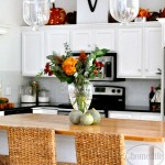 White kitchen cabinets with butcher block island. Beautiful white kitchen with subway tiles decorated for fall. Via First Home Love Life www.firsthomelovelife.com
